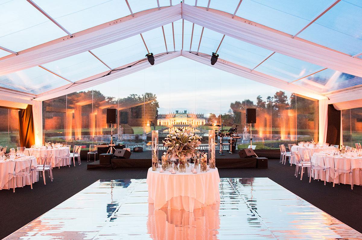 70° anniversario Ballin spa presso Villa Pisani allestito da Ferraro con 3 tende a due spioventi con teli crystal, struttura verniciata bianca, palco a speccio, tavoli rotondi, sedie crystal e mise en place
